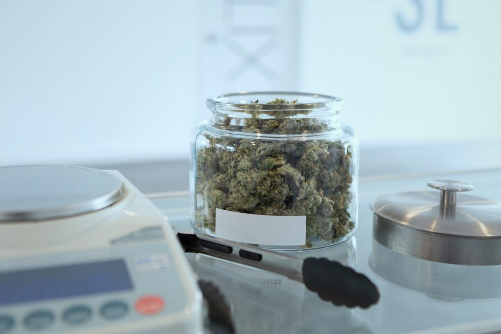 open glass jar of marijuana on a countertop beside a pair of tongs, with a scale for weighing weed in the foreground