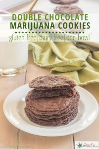 stack of gluten free double chocolate marijuana cookies on a white plate with a glass of milk and green tea towel in the background