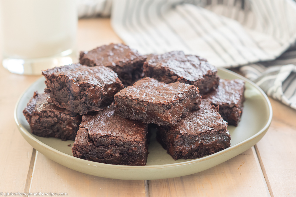 a plate full of gluten free pot brownies with chocolate chips on a light green plate on a wooden table with a glass of milk and a light green striped dish towel in the background